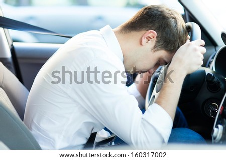 Exhausted driver resting on steering wheel  - stock photo