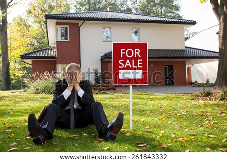 Exhausted estate agent sitting outside the house