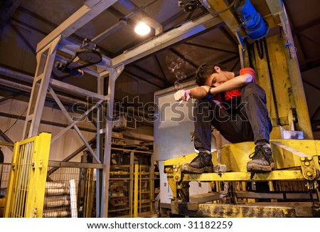 Exhausted factory worker smoking - stock photo