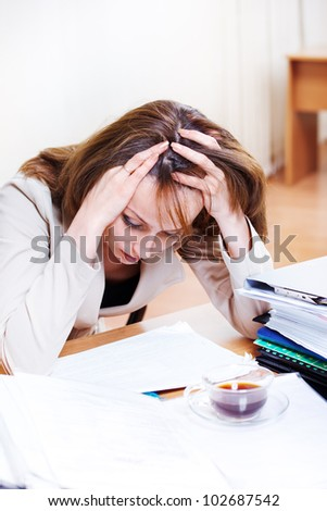 Exhausted female reading papers at office - stock photo