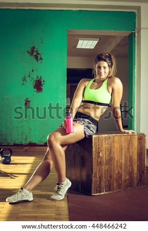 Exhausted gym girl drinking water after hard sweaty training in rustic old style gym. Toned image.