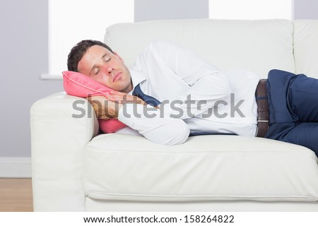Exhausted handsome businessman lying on couch after work at home - stock photo