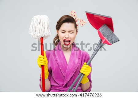 Exhausted hysterical young housewife with mop, cleaning brush and dustpan shouting and crying  - stock photo