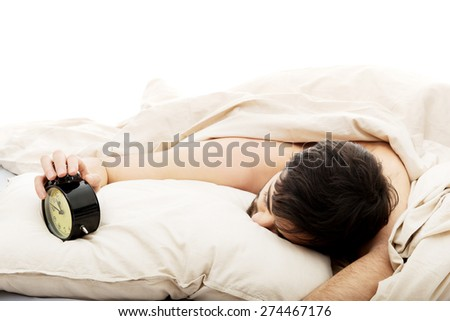 Exhausted man being awakened by an alarm clock in his bedroom. - stock photo