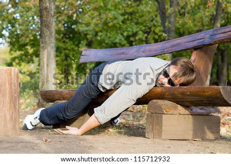 Exhausted man in casual clothing and sunglasses sleeping on a rustic wooden bench in woodland