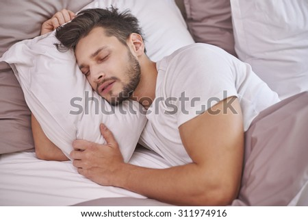 Exhausted man sleeping in his bed