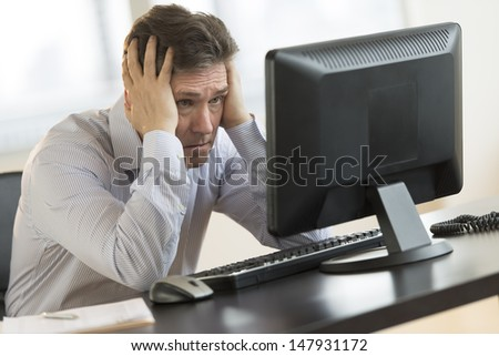 Exhausted mature businessman leaning while looking at computer monitor in office - stock photo