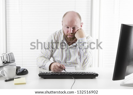 Exhausted office worker in the office. To much work and no motivation. - stock photo