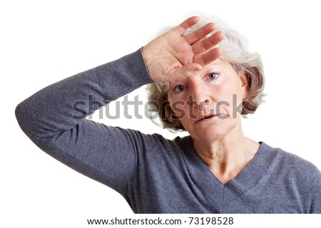Exhausted old senior woman holding hand to her forehead - stock photo