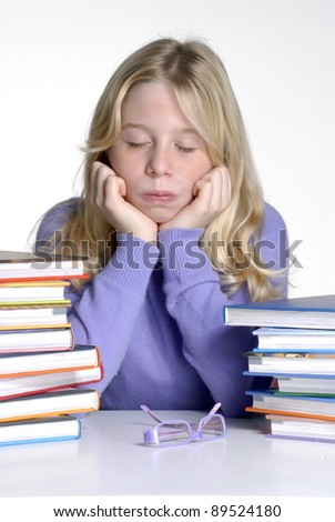 Exhausted school girl portrait behind books after studding. - stock photo