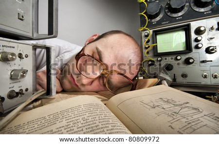 Exhausted scientist sleeping on book at vintage technological laboratory - stock photo