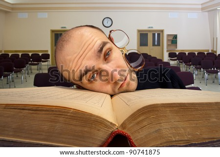 Exhausted sleepy student at empty university classroom - stock photo