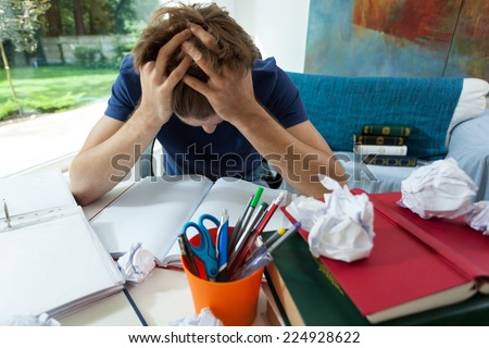 Exhausted student in blue t-shirt learning at home - stock photo