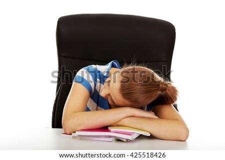 Exhausted teenage woman sleeping on the desk - stock photo