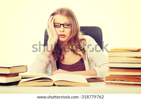 Exhausted teenage woman with stack of books