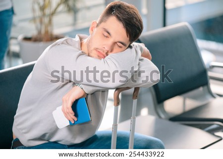Exhausted traveler. Tired handsome man in casual clothing sleeping on his luggage while sitting on the rows of chairs in the airport lobby with a ticket and passport in hand - stock photo