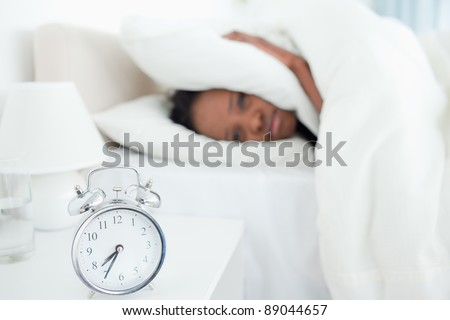 Exhausted woman covering her ears while her alarm clock is ringing in her bedroom - stock photo