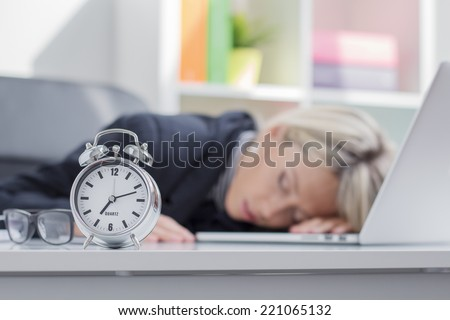 Exhausted woman sleeping in front of computer - stock photo