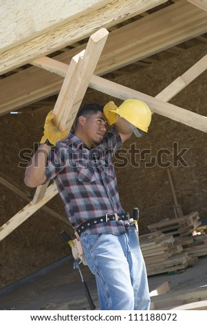 Exhausted worker carrying materials at a construction site - stock photo