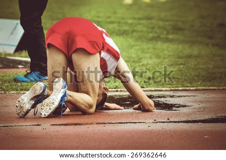 Exhausted young athlete falling on the ground after long run. Male runner on his knees on the running track after winning or loosing a race.  - stock photo