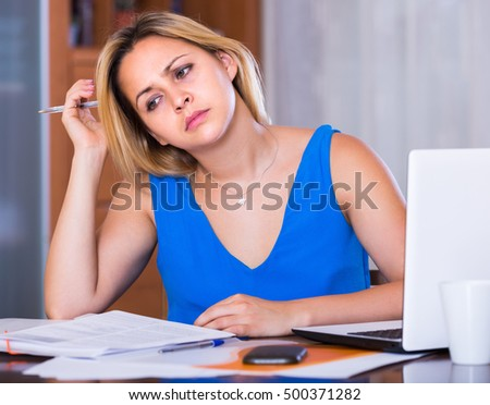 Exhausted young blonde woman making mistakes in her work