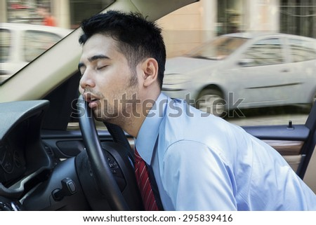 Exhausted young businessman sleeping in the car while driving the car on the road - stock photo