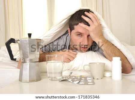 exhausted young Man in bed with coffee, water and tablets suffering hangover and headache - stock photo