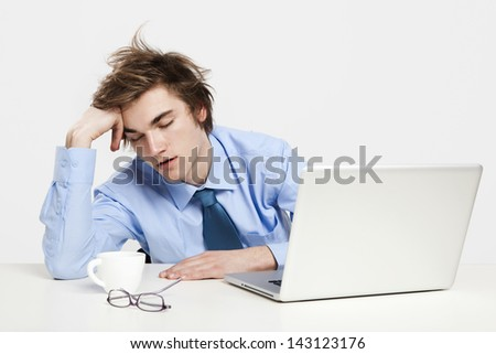 Exhausted young man in the office with the laptop on his front and sleeping