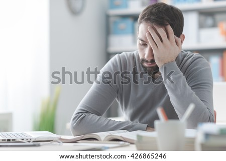 exhausted young man working at office desk and touching his head he is having a