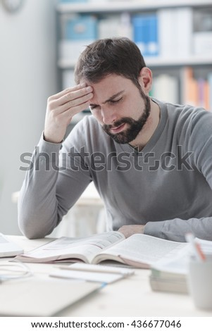 Exhausted young man working at office desk and touching his head, he is having a bad headache, stress and overwork concept