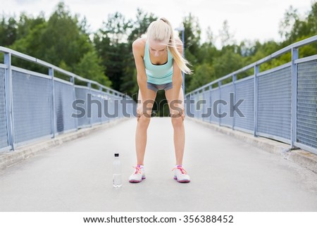 Exhausted young woman catching her breath after a long run - stock photo
