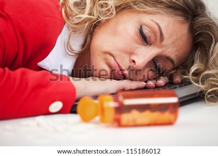 Exhaustion - woman asleep on computer keyboard with pills in foreground - stock photo