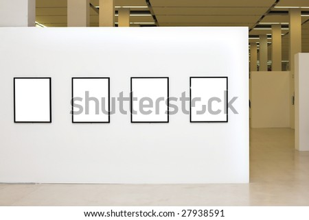Exhibition in museum with four empty frames on white walls - stock photo