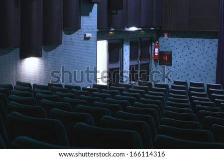 Exit doors in a dark blue movie theater (cinema), back to reality
