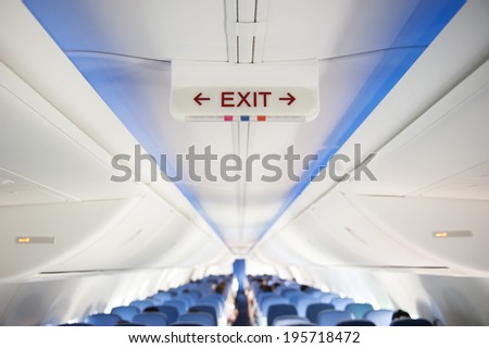 Exit sign in an aircraft interior - stock photo