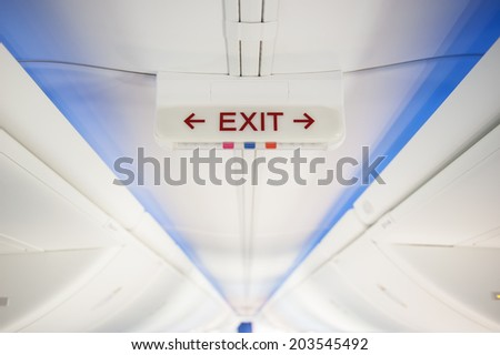 Exit sign in modern jet plane - stock photo