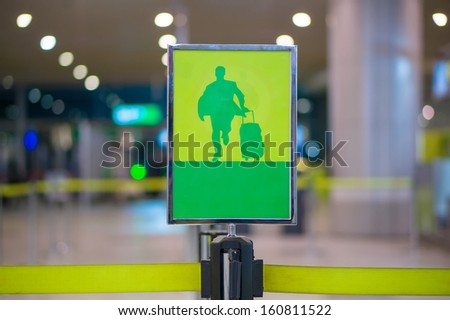 Exit sign - Man with luggage on waiting line at check in desk in airport - stock photo