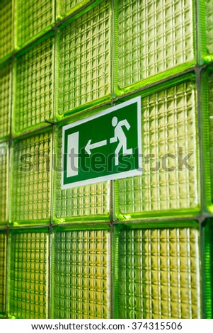 Exit Sign On Green Glass Wall - stock photo