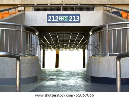 exit through tunnel in stadium with metal railings and a lot of light at the end of the tunnel - stock photo