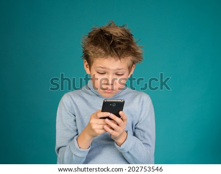 Exited child playing games on smartphone on blue background.  - stock photo