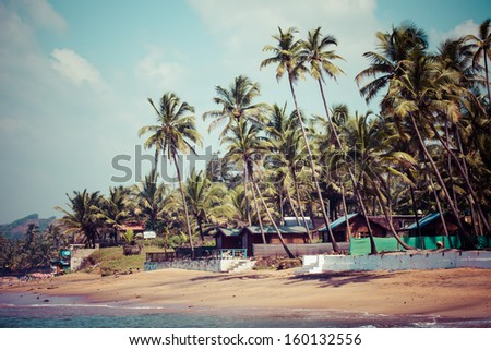 Exiting Anjuna beach panorama on low tide with white wet sand and green coconut palms, Goa, India  - stock photo
