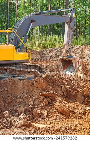exkavator digging clay ground on construction site in forest - stock photo