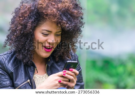 exotic beautiful young girl with dark curly hair using her cell phone texting and sitting in the garden - stock photo