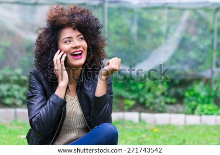 exotic beautiful young happy girl with dark curly hair using her cell phone sitting in the garden - stock photo