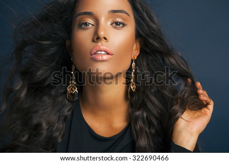 exotic female model with long curly black hair and bright makeup. Beauty and fashion portrait.Toned in warm colors, studio shot on blue background. horizontal. - stock photo