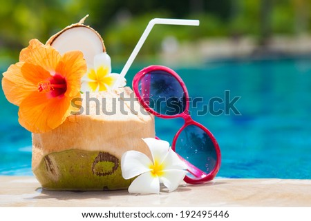 exotic fresh coconut shake and sunglasses by the tropical pool - stock photo