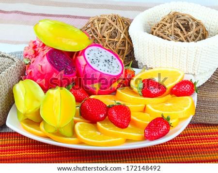 Exotic Fruit Dish with Dragon Fruit, pitahaya,strawberries and orange slices  - stock photo