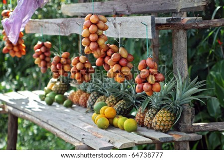 Exotic fruit stand in rain-forest : exotic fruit stand by the road in the middle of a rainforest of Madagascar. Focus on right side of image. - stock photo
