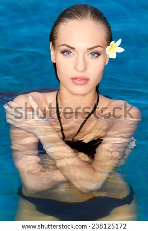 Exotic gorgeous young woman with frangipani in her hair standing chest high in the water in the swimming pool looking at the camera with a sensual expression - stock photo