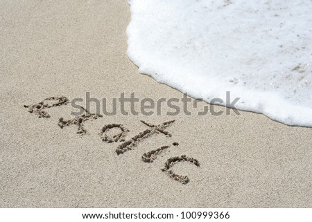 Exotic hand written in the sandy beach - stock photo
